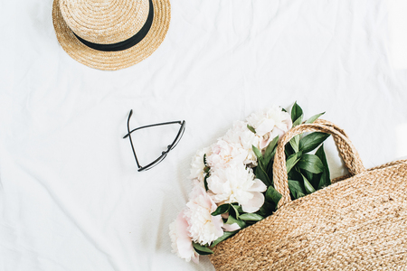 Minimal female background with straw hat, glasses, white peony flowers bouquet in bag. Flat lay, top view.