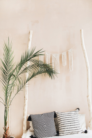 Minimal home interior design. Tropical palm branches, pillows and bed with boho style decoration at pastel beige wall. Stock Photo