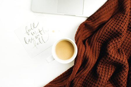 """Espace de travail avec citation manuscrite """"Tomber amoureux de l'automne"""", ordinateur portable, café, pull chaud sur fond blanc. Bureau de bureau automne plat Lapointe, vue de dessus."""