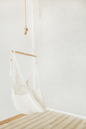 Cozy white hammock in white room. Minimal home interior design. Stock Photo