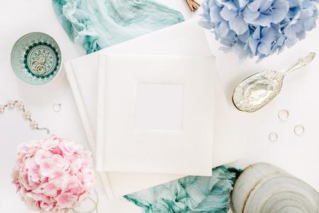 Family wedding photo album, pastel colorful hydrangea flower bouquet, turquoise blanket, decoration on white background. Flat lay, top view festive mockup. Stock Photo