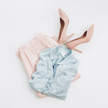 Woman pastel clothes: jeans shirt, skirt, high-heel shoes on white background. Flat lay, top view female fashion collage. Standard-Bild