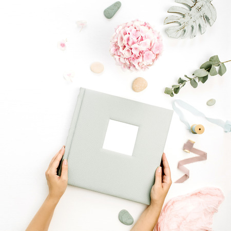 Female hands hold wedding or family photo album. Composition with hydrangea flower bouquet, eucalyptus branch, pastel pink blanket, monstera leaf plate on white background. Flat lay, top view. Stock Photo