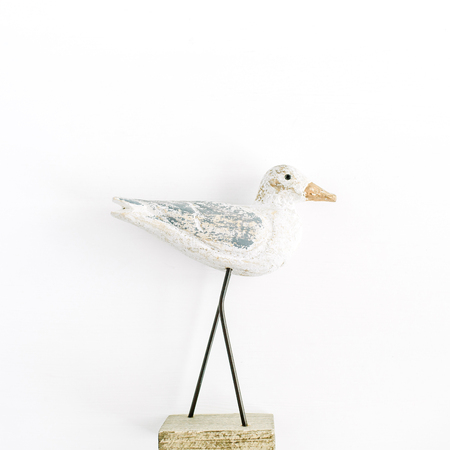 Trendy interior figurine wooden bird on white background. Flat lay, top view sculpture.