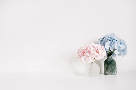 Pink and blue hydrangea flower bouquets on white background. Minimal interior design floral concept.