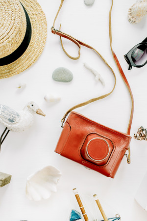 Creative composition with bird figurine, toy boat, retro camera, sunglasses, seashells and straw hat on white background. Flat lay, top view lifestyle blog concept. Stock Photo
