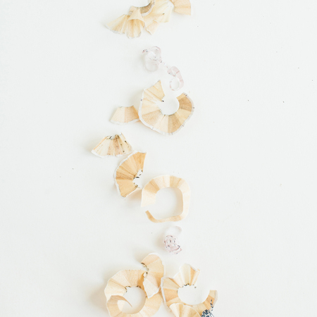 Pencil shavings on white background. Flat lay, top view.