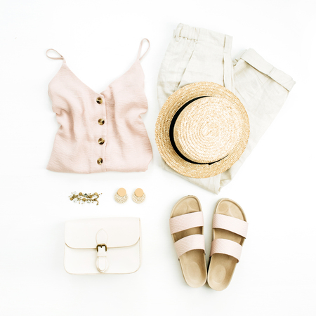 Flat lay, top view travel fashion boho style look with woman clothes and accessories. Straw hat, slippers, purse, blouse, bracelet, earrings, pants on white background. Stock Photo