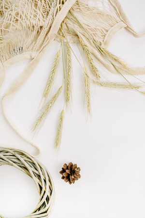 Rye ears in string bag, wreath frame and cone on white background. Flat lay, top view fall autumn composition. Stockfoto