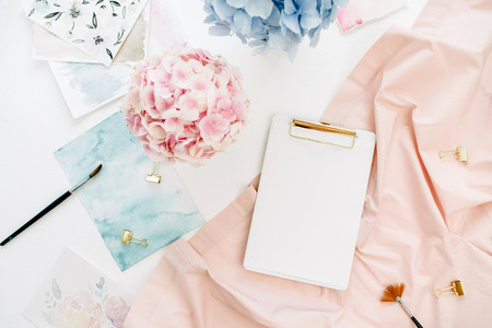 Art composition home office desk workspace with copy space clipboard, pastel hydrangea flowers bouquet, watercolor painting, peachy blanket. Flat lay, top view.