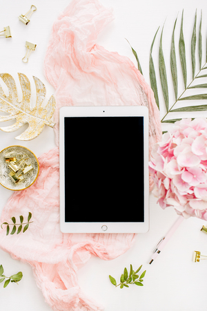Modern home office desk workspace with blank screen tablet, pink hydrangea flowers bouquet, tropical palm leaf, pastel blanket, monstera leaf plate and accessories on white background. Flat lay, top view rose gold mockup.