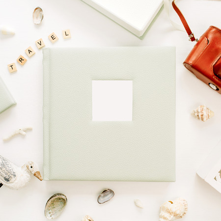Travel styled composition with photo album, retro camera, bird sculpture on white background. Flat lay, top view traveler blog hero header.