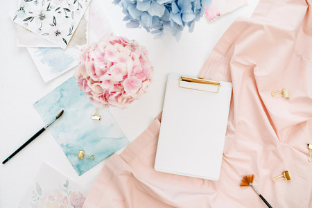 Watercolor artist home office desk workspace with copy space clipboard, pastel hydrangea flowers bouquet, watercolor painting, peachy blanket. Flat lay, top view.