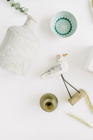 Trendy interior decorations. Bird, plate, candlestick, vase. Flat lay, top view background. Stock Photo