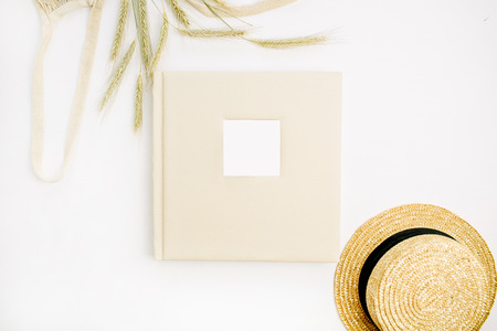 Wedding or family photo album, rye ears, straw hat on white background. Flat lay, top view mock up. Stock Photo