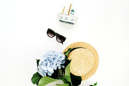 Blue hydrangea flower, straw hat, sunglasses, toy boat on white background. Flat lay minimal travel concept. Stock Photo
