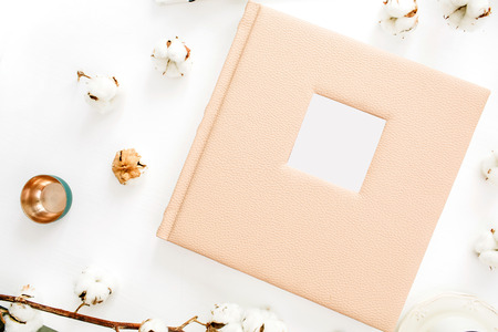 Family or wedding photo album with blank space for text, cotton buds, decoration on white background. Flat lay, top view.
