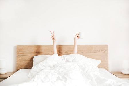 Handen van jonge vrouw met koffiemok in bed met wit linnengoed. Minimaal gelukkig ochtendconcept. Stockfoto
