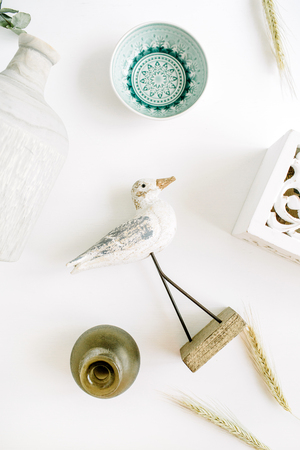Modern interior design decoration background with bird, plate, candlestick, vase. Flat lay, top view. Stock Photo