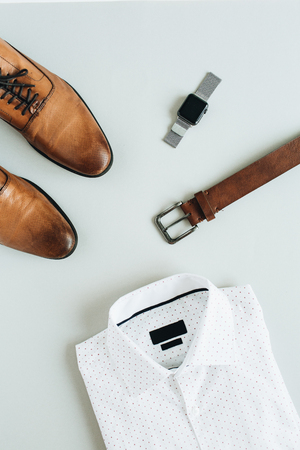 Mens fashion composition with watch, shirt, belt and shoes. Flat lay, top view.