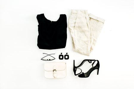 Flat lay, top view fashion collage with female clothes and accessories. High heel shoes, purse, blouse, glasses, earrings, pants on white background. Minimal concept.