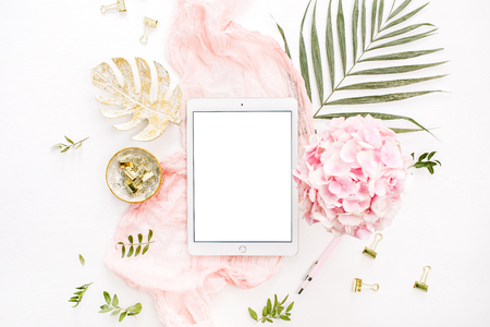 Blank screen tablet, pink hydrangea flowers bouquet, tropical palm leaf, pastel blanket, monstera leaf plate and accessories on white background. Flat lay, top view rose gold home office desk workspace mockup. Foto de archivo - 110370563