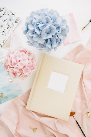 Family wedding photo album, pastel colorful hydrangea flower bouquet, peachy blanket, decoration on white background. Flat lay, top view.