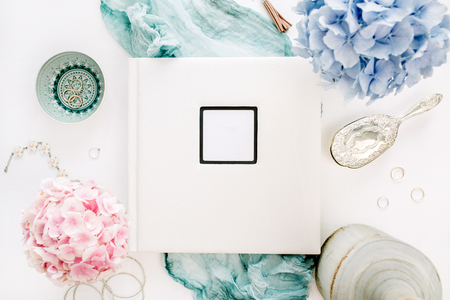 Family wedding photo album, pastel colorful hydrangea flower bouquet, turquoise blanket, decoration on white background. Flat lay, top view. Stock Photo