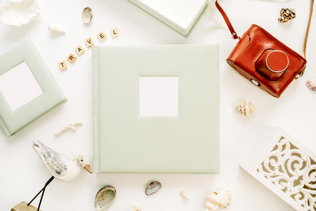 Travel styled composition with photo album, retro camera, bird sculpture on white background. Flat lay, top view travel blog hero header.