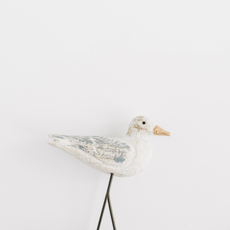 Trendy stylish interior figurine wooden bird on white background. Flat lay, top view sculpture. Stock Photo