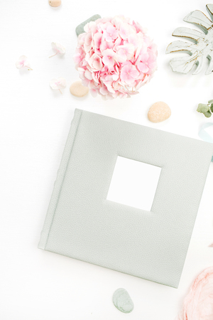 Composition with wedding or family photo album, pink hydrangea flower bouquet, monstera leaf plate on white background. Flat lay, top view.