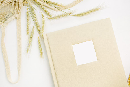 Wedding or family photo album, rye ears on white background. Flat lay, top view mock up. Stock Photo