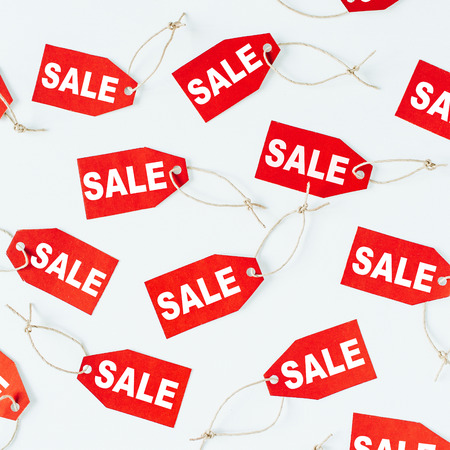 Black Friday sales discount composition. Red tags with word SALE on white background. Flat lay, top view.
