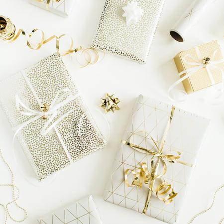Cajas de regalo de oro, decoraciones sobre fondo blanco. Vista plana endecha, superior Navidad, concepto de empaquetado de regalos de vacaciones de año nuevo.