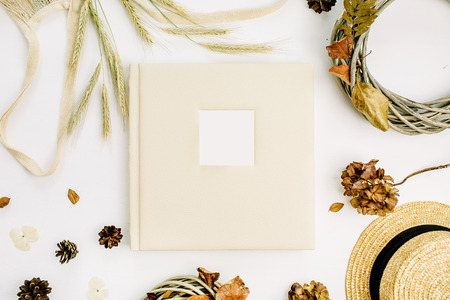 Fall autumn composition with wedding or family photo album, wreath frame, string bad, rye ears, cones, dry leaves on white background. Flat lay, top view mock up. Stock Photo