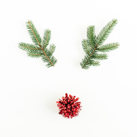 Christmas, New Year minimal concept. Christmas deer symbol made of fir branches and red bow isolated on white background. Flat lay, top view. Stock Photo