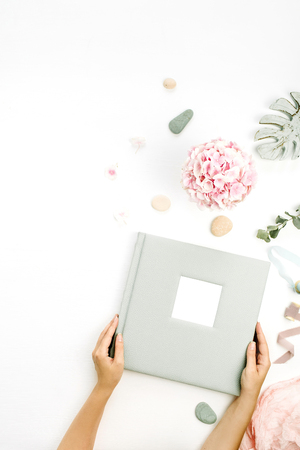 Woman hands holding wedding or family photo album. Hydrangea flower bouquet, eucalyptus branch, pastel pink blanket, monstera leaf decor on white background. Flat lay, top view.