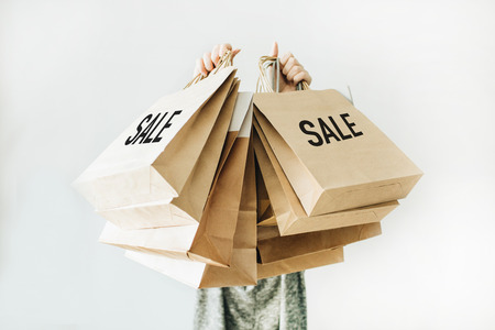 Black Friday sales discount concept. Young woman hold craft paper bags with word Sale on white background. Stockfoto