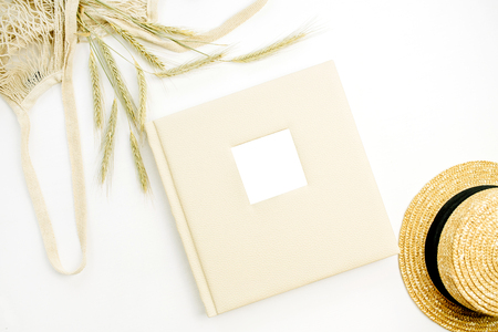 Wedding or family photo album, rye ears in string bag, straw hat on white background. Flat lay, top view mock up.