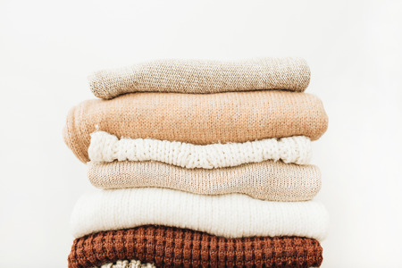 Closeup of warm winter sweaters and pullovers. Woman clothes minimal fashion pattern.