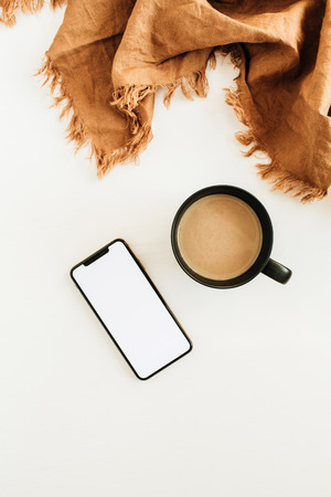 Mug of coffee with milk, brown blanket, smart phone with blank screen mockup on white background. Flat lay, top view. Foto de archivo