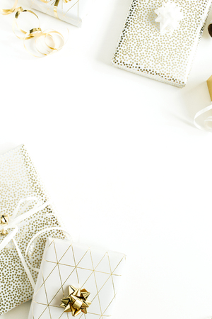 Marco de borde de Navidad, composición de vacaciones de año nuevo con cajas de regalo doradas, decoraciones sobre fondo blanco. Vista plana endecha, superior del embalaje de regalos. Foto de archivo