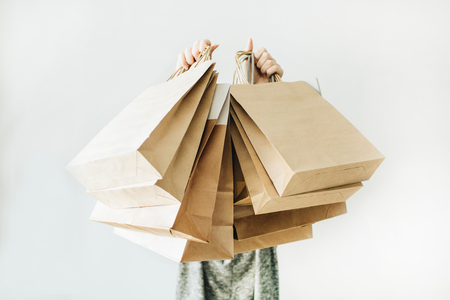 Black Friday sales discount concept. Young woman hold craft paper bags with word Sale on white background. Stok Fotoğraf