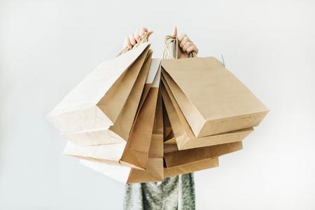 Concepto de descuento de ventas de viernes negro. Mujer joven mantenga bolsas de papel artesanal con la palabra Venta sobre fondo blanco. Foto de archivo