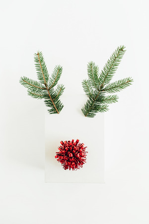 Christmas, New Year minimal concept. Christmas deer symbol made of gift box, fir branches and red bow isolated on white background. Flat lay, top view.