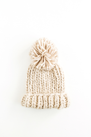 Warm female knitted hat isolated on white background. Flat lay, top view minimal fashion concept.