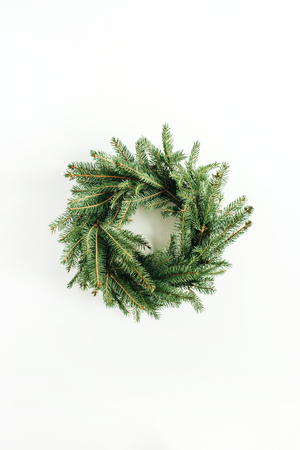 Wreath frame made of fir branches on white background. Flat lay, top view minimalist Christmas composition. Imagens
