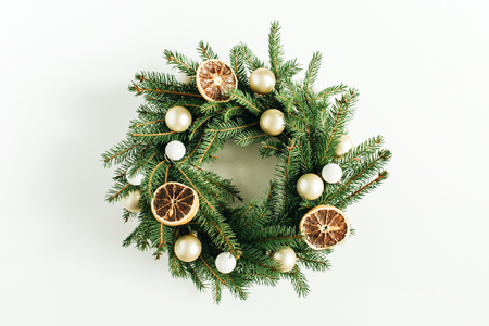 Christmas, New Year wreath frame made of fir branches decorated with dried oranges and Christmas balls on white background. Flat lay, top view blog hero header. Фото со стока - 112605229