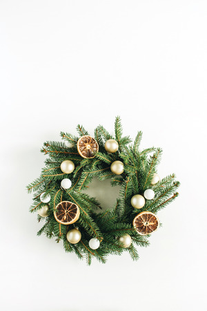 Christmas, New Year wreath frame made of fir branches decorated with dried oranges and Christmas balls on white background. Flat lay, top view minimal composition. Фото со стока