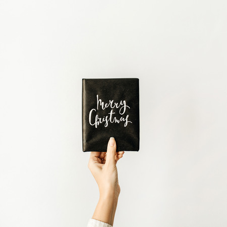 Gift box with quote MERRY CHRISTMAS in woman hand on white background. Christmas composition. Flat lay, top view.